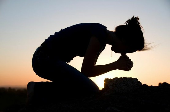 woman bowing in prayer